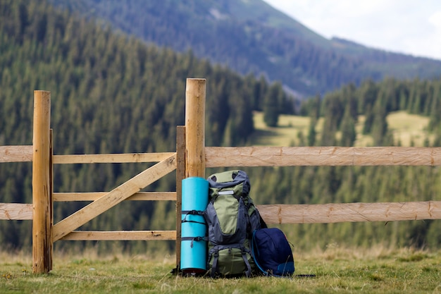 Big tourist backpack and a small one leaned at low wooden fence on lit by sun grassy valley on mountains covered with dense forest blurred scene. tourism, camping and traveling concept.