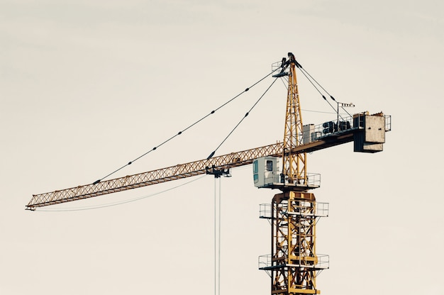 Big tower crane against sky in faded tones.  construction equipment close-up with copyspace. build of city.