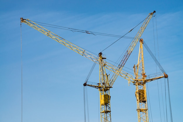Big tower cranes against the blue sky. image of construction equipment close-up with copy space. build of city.