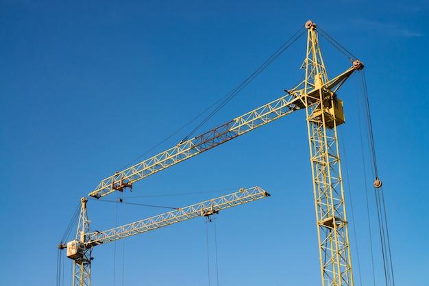 Big tower cranes against the blue sky.