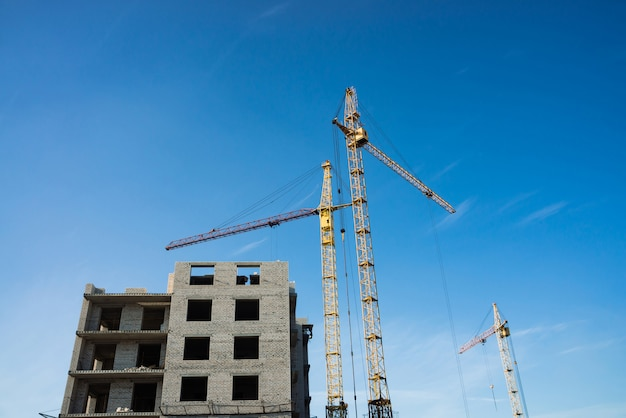 Big tower cranes above buildings under construction against blue sky. image of construction close-up with copy space. build of city.