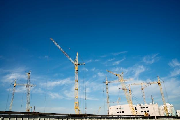 Big tower cranes above buildings under construction against blue sky.