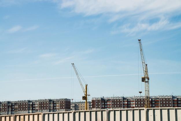 Big tower cranes above buildings under construction against blue sky