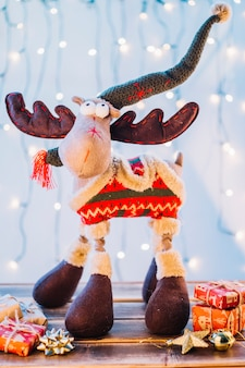 Big toy deer with gift boxes on table