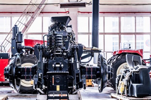 Установка колес большого трактора в сборочном цехе на промышленном предприятии