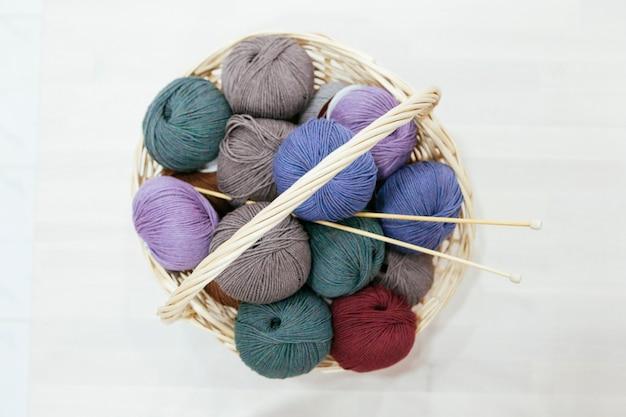 다양한 원사와 뜨개질 바늘로 된 큰 전통 바구니
