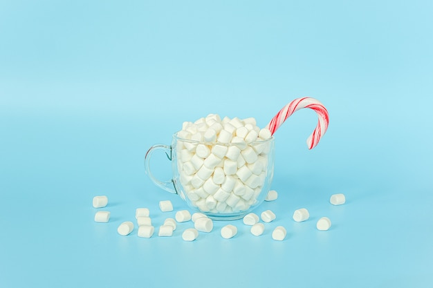 Big transparent cup of marshmallows with red lollipop cane on blue wall. merry christmas or happy new year concept.