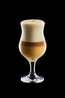 Big transparent glass with layered latte isolated on black background