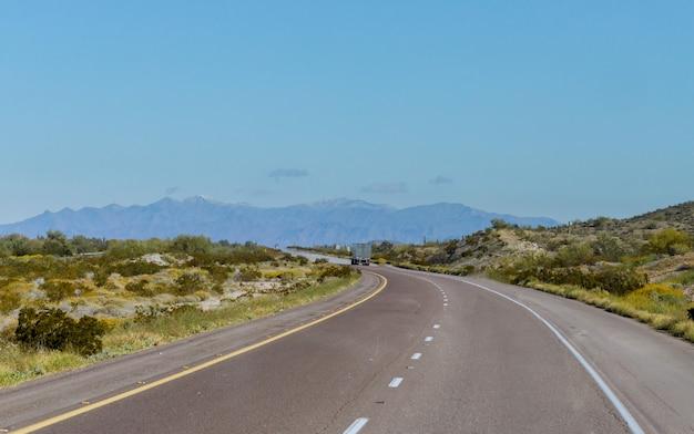 구불 구불 한 산악 도로에서 달리는 큰 트럭 장비 강력한 대중적인 산업 고전적인 반 트럭