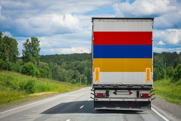 高速道路上を移動するアルメニアの国旗が付いている大きなトラック