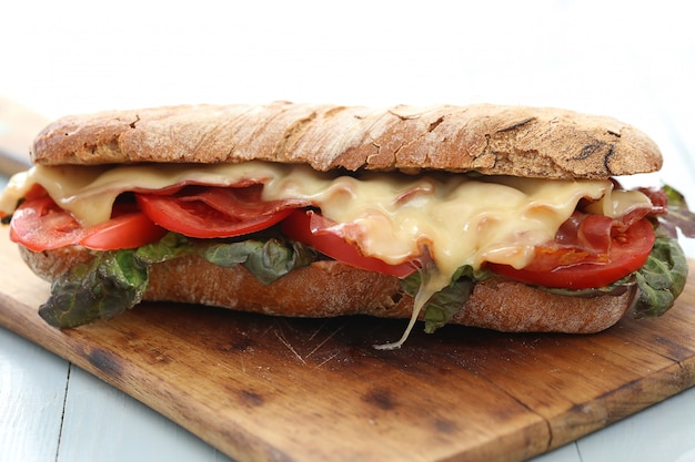 Big vegan sandwich with vegetables and cheese on wooden board table