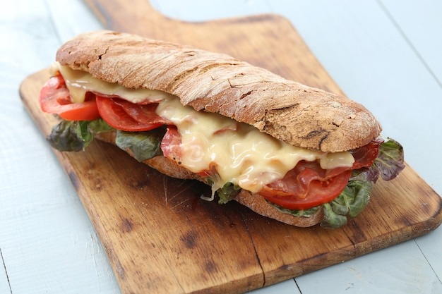 Big vegan sandwich with vegetables on wooden board table