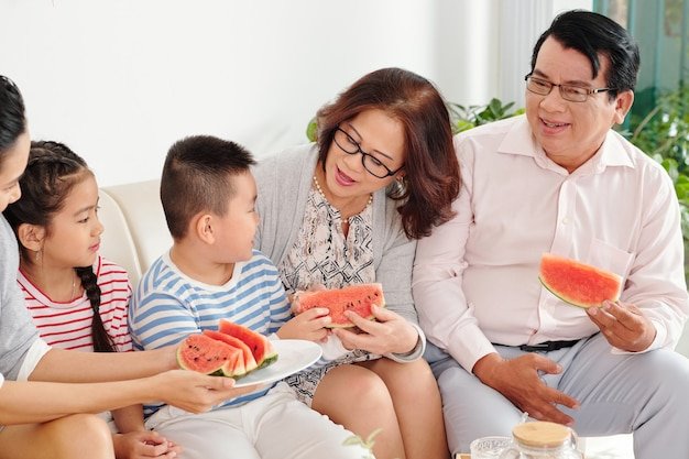 Big vietnamese family gathered at home to eat fresh ripe watermelon and celebrating lunar new year