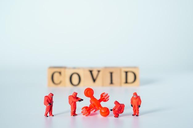 특수 의료 부대 미니어처 피규어 팀이 있는 큰 바이러스, 위험한 치명적인 바이러스 유형에 대한 조치를 준비하는 팀, 흰색 배경에 '코비드'라는 단어가 있는 나무 큐브.