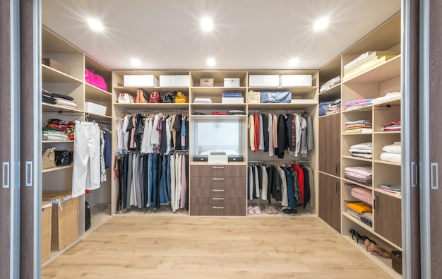 Big wardrobe with different clothes for dressing room