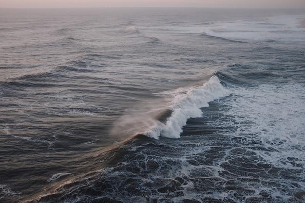 Большая волна разбивается на закате