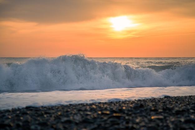 Большие волны и закат на берегу, романтический вечер