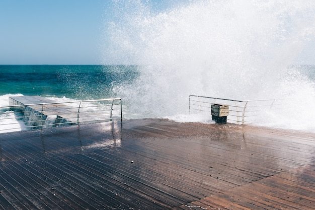 Big waves break about the quay