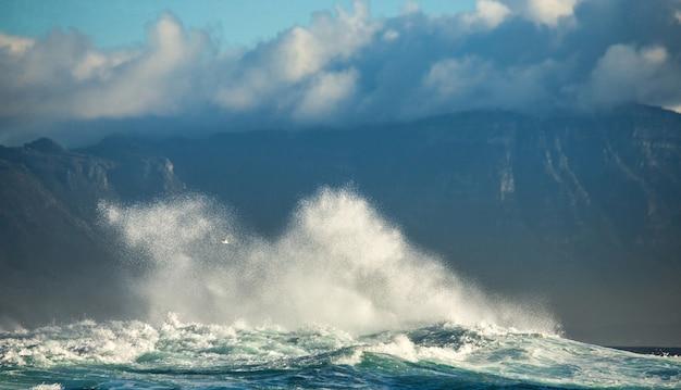 Большие волны разбиваются о скалы в море на фоне береговой линии.