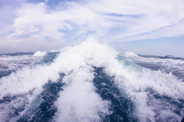 Большие волны от двигателя за катером в открытом море голубое небо с белыми облаками