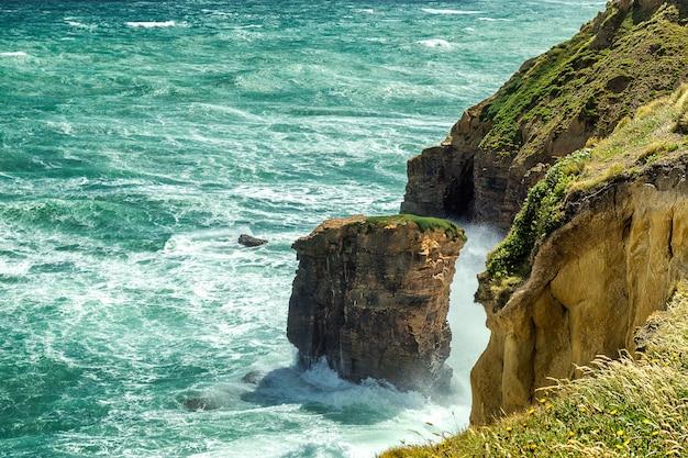 ニュージーランド、オタゴの砂の崖に押し寄せる白い泡の大きな波