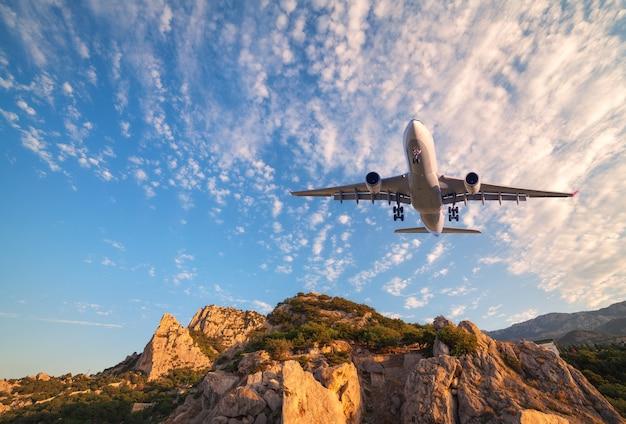 大きな白い飛行機が日の出の岩の上を飛んでいます。