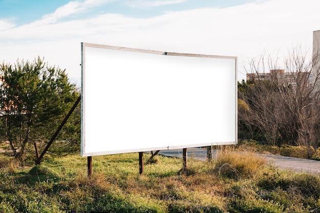 Big white billboard on green roadside