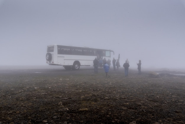 Big white bus and a group of people near it in foggy weather in iceland
