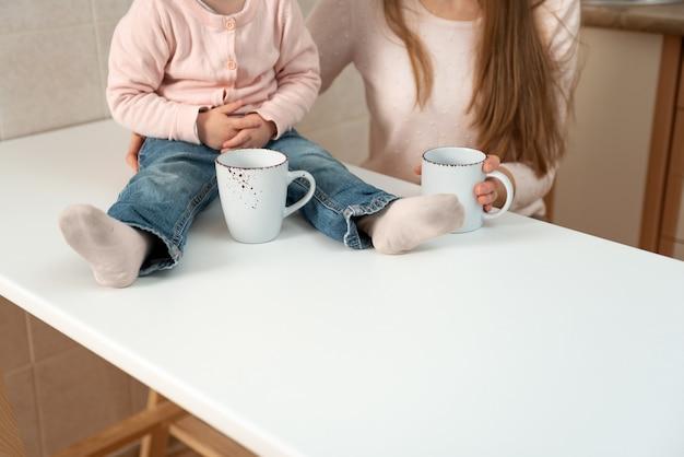 Большие белые чашки в женских и детских руках. завтрак в семье, подробности.