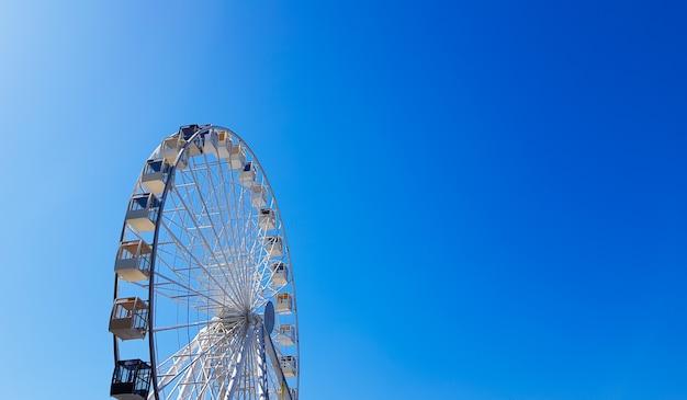 Большое белое колесо обозрения на фоне голубого неба. часть аттракциона на синем фоне с копией пространства. кабины, смотровые площадки.