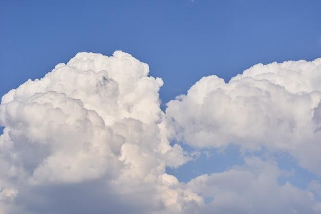 明るい晴れた日に青い空に浮かぶ大きな白いふわふわ積乱雲