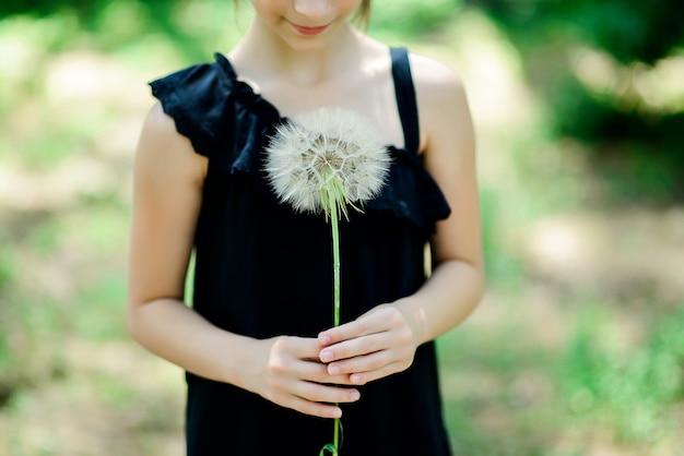 Большой белый пушистый одуванчик в руках ребенка на летнем зеленом фоне