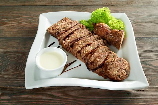 Un grande piatto bianco, pieno di fette di carne ripiene con salsa all'aglio e decorato con foglie di insalata. buon antipasto per la cena al ristorante con vino rosso.