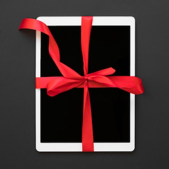 Big white tablet with red ribbon