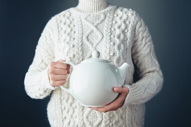 Grande tapot bianco con tè in mano in aria. irriconoscibile donna indossava un maglione lavorato a maglia spessa bianca. vista frontale.
