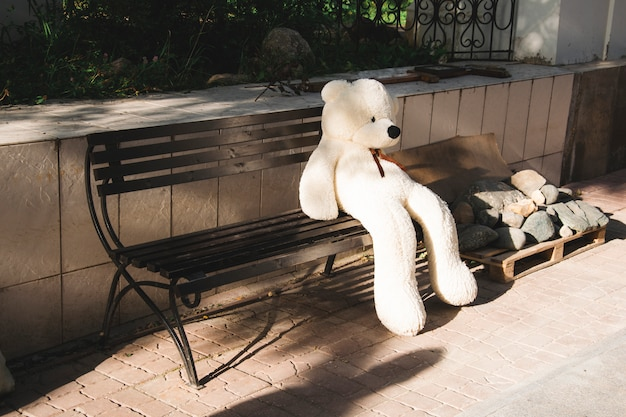 A big white teddy bear sits alone on a bench