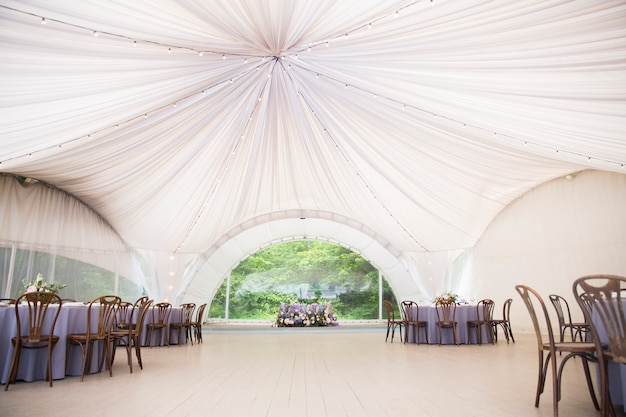 Big white wedding tent with beautiful decorations. tables with floral decorations and wooden chairs
