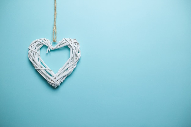 Big white wooden wicker heart on the rope with copy space. saint valentine's day card on blue background.