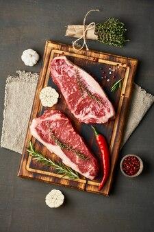 Big whole piece of raw beef meat. seasoning steak with salt, thyme, garlic.