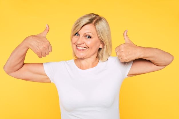 Большая победа! счастливая взволнованная улыбающаяся красивая старшая женщина показывает палец вверх и смотрит в камеру