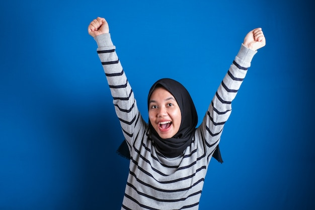 Big win. joyful asian student girl in headscarf celebrating success with raised hands and clenched fists over blue background with free space