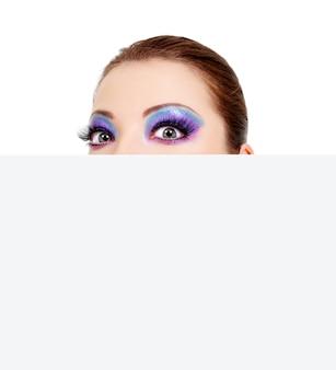 空白の白いバナーの外を見ている大きな不思議な女性の目