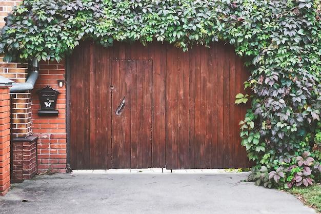 Большие деревянные ворота с зелеными листьями альпиниста плюща. частная собственность