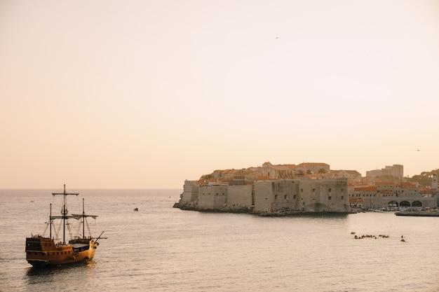 Большой деревянный корабль плывет в сторону старого города дубровника на закате