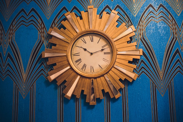 Big wooden vintage alarm clockon blue wallpaper background, painted of white and blue color on the wooden wall as background. interior design concept.
