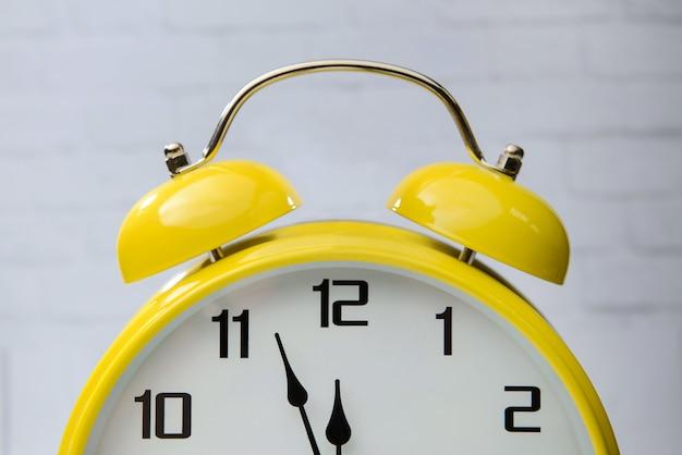 Большой желтый будильник с стрелками крупным планом.