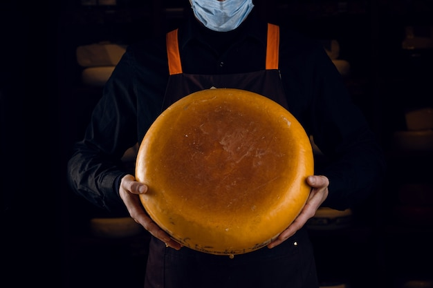 Big yellow cheese wheel in hands. seller in mask for protection against coronavirus covid-19. holding round cheese.