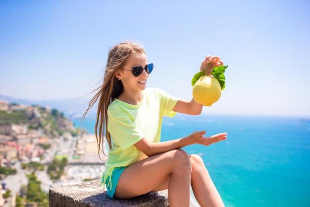 Big yellow lemon in hand in mediterranean sea and sky.