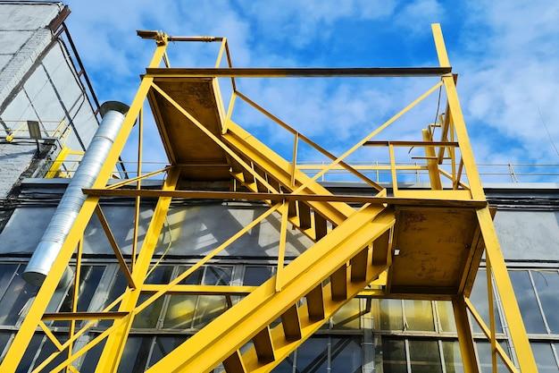 산업 공장 건물 근처 큰 노란색 계단