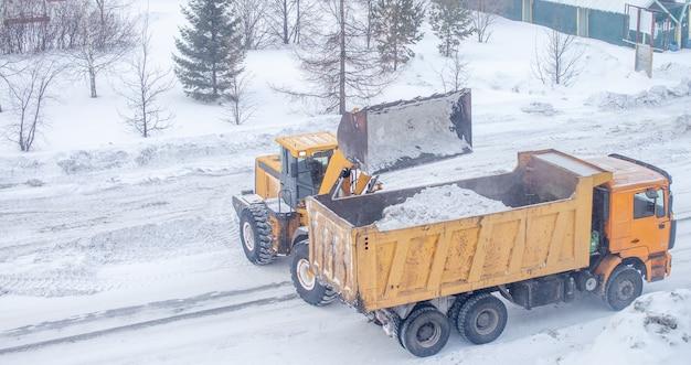 Большой желтый трактор убирает снег с дороги и загружает его в грузовик.